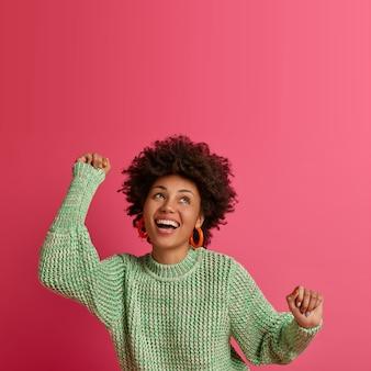 Colpo verticale di giovane donna spensierata che balla da campione, guarda con un ampio sorriso, concentrato sopra, gode di una perfetta giornata libera, si sente vincitrice, indossa un maglione caldo, isolato sul muro rosa