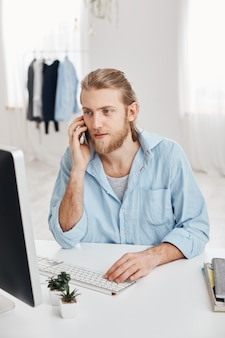 Vertical shot of caucasian handsome freelancer with beard and fair hair checking information and typing promotional text. pleasant looking male employee has phone conversation with clients.
