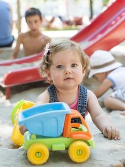 Colpo verticale di un bambino caucasico che gioca con i giocattoli su un parco giochi sabbioso