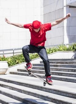 Colpo verticale di un maschio caucasico che salta su uno skateboard