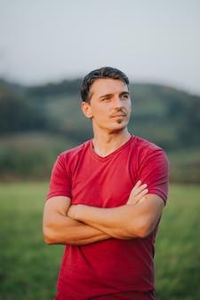 Colpo verticale di un maschio caucasico con una maglietta rossa