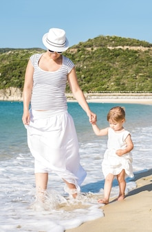 Vertical shot of a caucasian mother walking on the beach with her daughter during daylight
