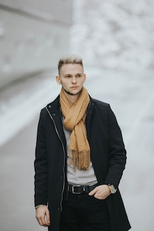 Vertical shot of a caucasian stylish male posing outdoors in a snowy city