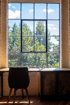 Vertical shot of a chair and a desk near a large window with an amazing view of greenery outside