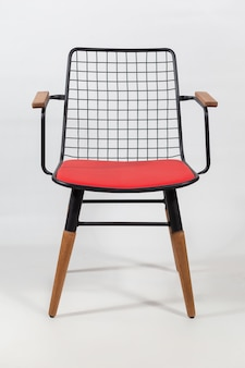 Vertical shot of a chair with a net on a chair's back behind a white surface