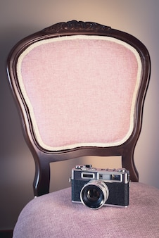 Vertical shot of a chair with a vintage photo camera on it