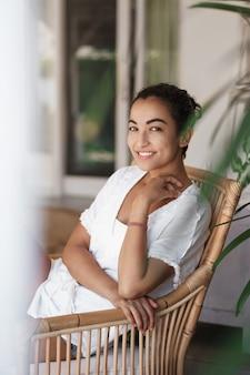 ラタンドアームチェアに座っている白いtシャツで日焼けしたブルネットの女性を笑顔で魅力的な垂直ショット