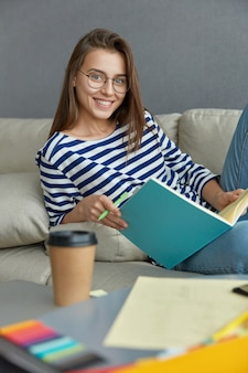 Vertical shot of cheerful brunette woman checks course work, reads text information, from textbook, holds pen, smiles happily, sits at couch drinks take out beverage. hipster student learns something