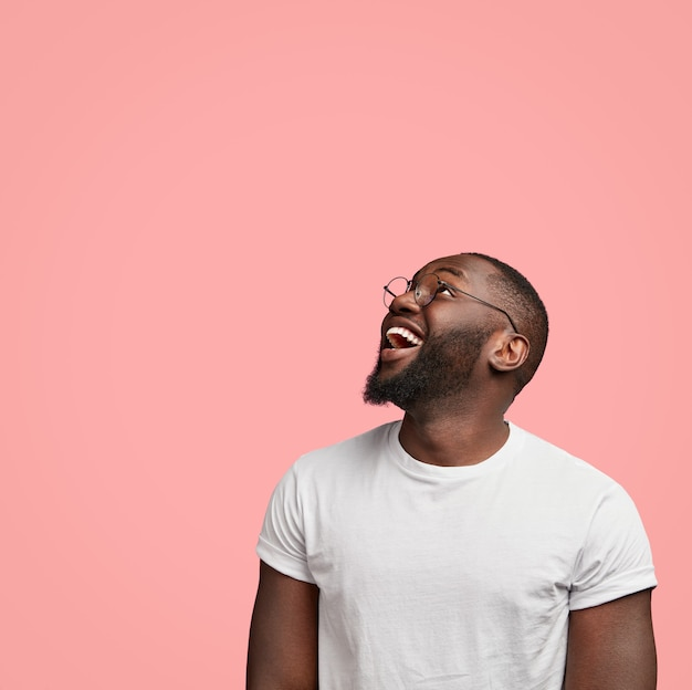 Vertical shot of cheerful dark skinned unshaven man looks positively upwards, being in good mood,