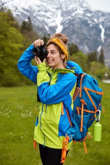 Vertical shot of cheerful female traveler focuses on scenic nature view