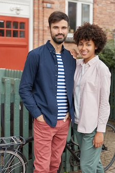 Vertical shot of cheerful mixed race couple have date, stand closely to each other near bicycles, fence and brick house