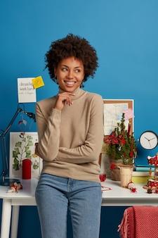 Colpo verticale della studentessa afroamericana allegra e soddisfatta si trova vicino al posto di lavoro contro il muro blu., tiene la mano sotto il mento e distoglie lo sguardo, pensa ai piani futuri felice di lavorare da casa