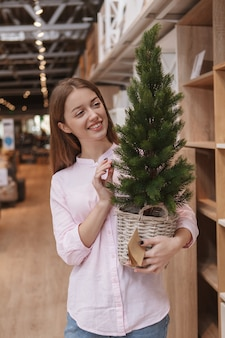 Vertical shot of a cheerful woman buying x-mas tree at home goods supermarket