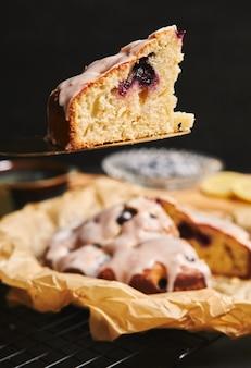 Colpo verticale di una torta di ciliegie con panna e ingredienti sul lato nero