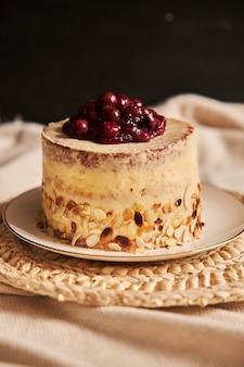 Colpo verticale di una torta di ciliegie con crema sul piatto bianco