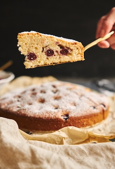 Vertical shot of a cherry cake with sugar powder and ingredients on black