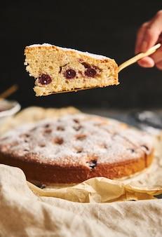 Colpo verticale di una torta di ciliegie con zucchero in polvere e ingredienti sul nero