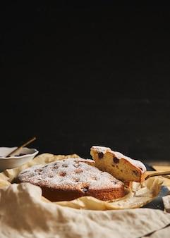 Colpo verticale di una torta di ciliegie con zucchero in polvere e ingredienti sul lato nero