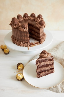 Vertical shot of a chocolate cake and a slice on a plate next to some pieces of chocolate