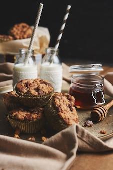 Colpo verticale di muffin al cioccolato con miele e latte