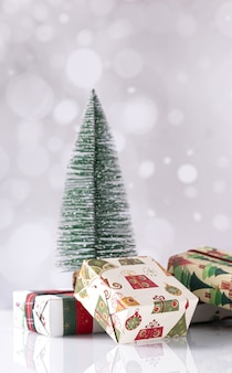 Vertical shot of christmas gift boxes and small tree