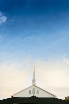 Vertical shot of a church with a blue cloudy sky