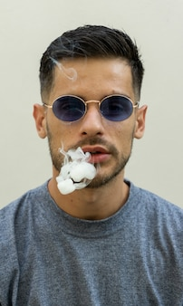 Vertical shot of cigarette smoke getting out of a young caucasian male in sunglasses
