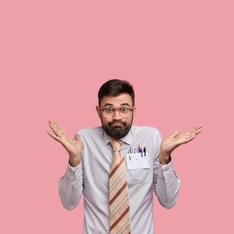 Colpo verticale di un uomo caucasico dubbioso senza tracce con la barba ispida ha un aspetto incerto, indossa camicia e cravatta formali