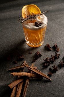 Vertical shot of a cocktail with an orange slice and dry herbs near a cinnamon sticks