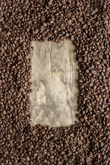 Vertical shot of a coffee beans frame over a wooden surface great for background or writing text
