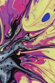 Colpo verticale di uno sfondo colorato di vernice acrilica creativa e miscela liquida di olio