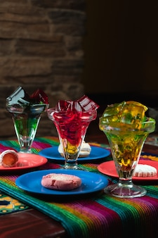 Vertical shot of colorful sweet jelly desserts next to cookie plates