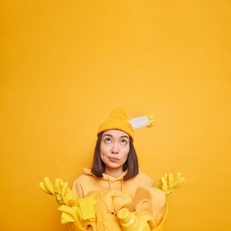 Vertical shot of confused asian woman spreads palms focused above with indecisive expression doesnt know from what to start cleaning wears rubber gloves does laundry at home isolated on yellow wall