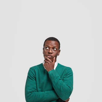 Vertical shot of contemplative thoughtful dark skinned man keeps hand under chin, looks thoughtfully upwards