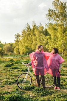 Vertical shot of a couple sharing a pink plastic raincoat at a date with a bike
