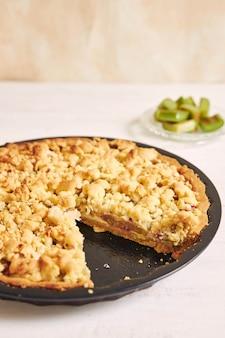 Ripresa verticale di una crostata di torta rhabarbar croccante e alcuni ingredienti su un tavolo bianco