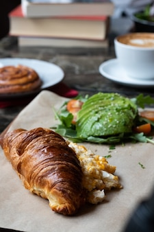 Vertical shot of a croissant with eggs and fresh avocadoes on a parchment paper