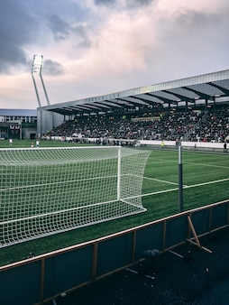 Vertical shot of crowded soccer stadium under cloudy sky