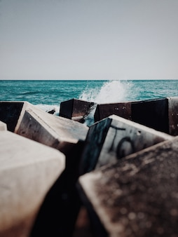 Vertical shot of cubical rubbles and trash in the body of water in the ocean