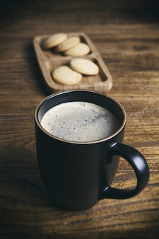 Vertical shot of a cup of black coffee and cookies