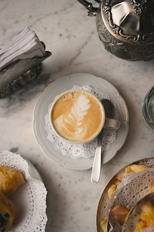 Colpo verticale di una tazza di cappuccino sul tavolo di marmo con dessert