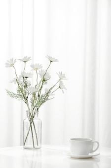 Vertical shot of a cup of coffee next to a vase full of beautiful white flowers, indoors