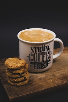 Vertical shot of a cup of coffee with some cookies on a wooden tray in a dark studio