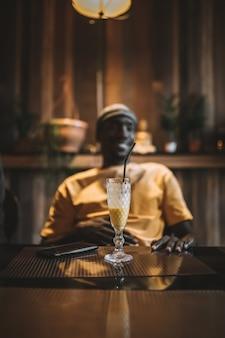 Colpo verticale di una tazza di frullato su un tavolo davanti a un maschio afroamericano