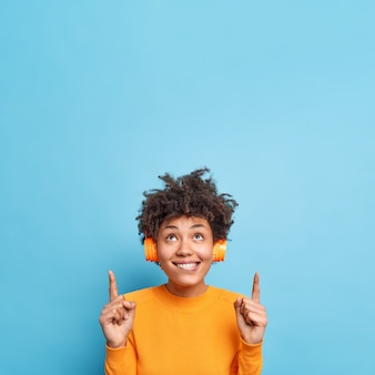 Vertical shot of curious curly haired young woman bites lips wears stereo headphones for listening music points upwards shows shopping deal or promotional offer isolated over blue wall