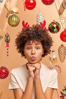 Vertical shot of curly haired woman keeps lips folded and hands under chin looks with romantic expression at camera dressed casually surrounded by christmas toys has festive mood. holiday celebration