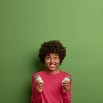 Vertical shot of curly positive woman looks above with smile, holds delicious white organic yoghurt, wears casual pink jumper, poses against green wall, empty space upwards. healthy nutrition