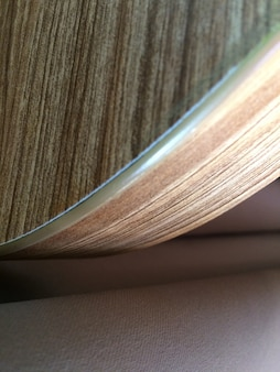 Vertical shot of curved plywood near a light pink mattress