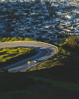 Vertical shot of a curvy road down the hill with buildings in the distance
