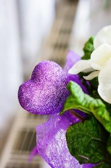 Colpo verticale di un cuore viola decorativo con glitter